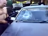 Crazy guy smashes car windscreen with his head