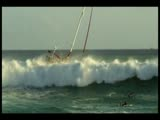 Sail boat taking on big surf
